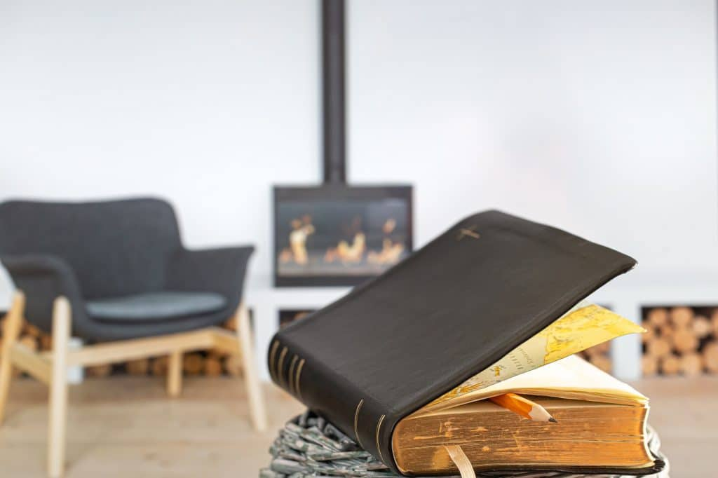 Bible book with pencil, on the background of the living room.