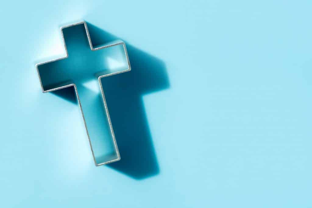 Church worship, salvation concept. Silhouette of christian cross on blue background, soft bokeh